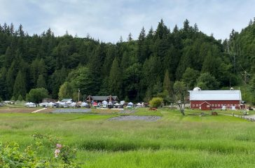 Red barn in distance with farmers market to left