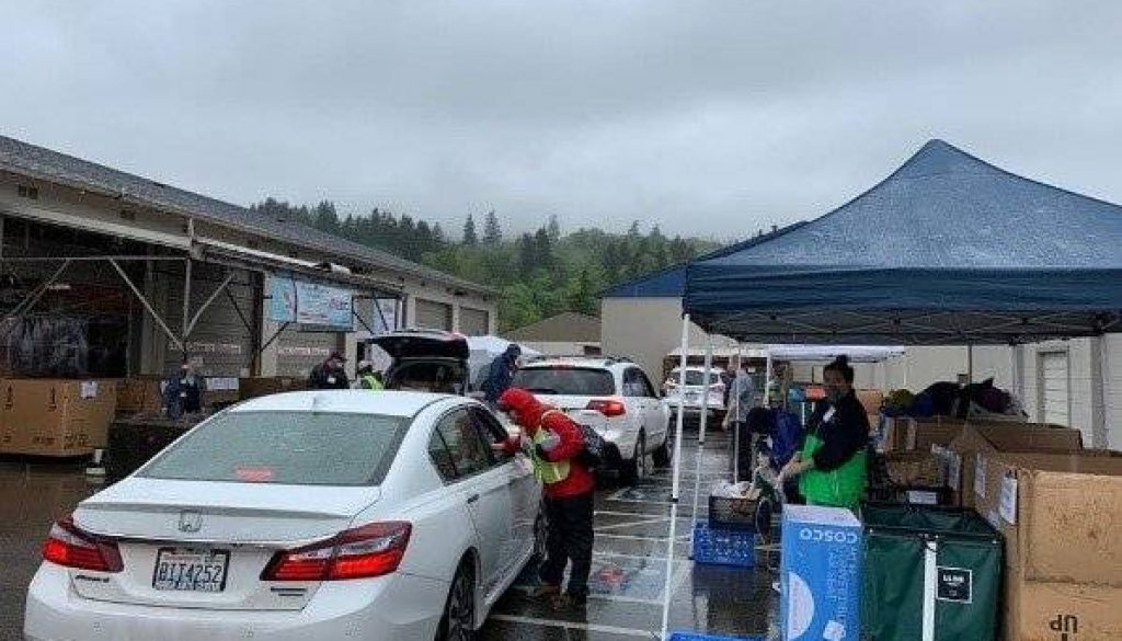 White car pulls up to food bank to pickup groceries