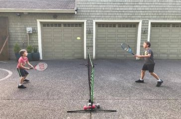 Two kids playing tennis on their driveway
