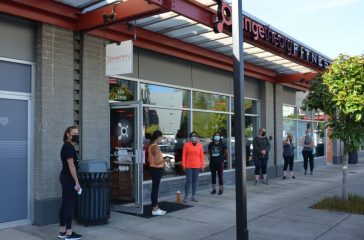 Patrons lining up waiting for Orange Theory's doors to open.