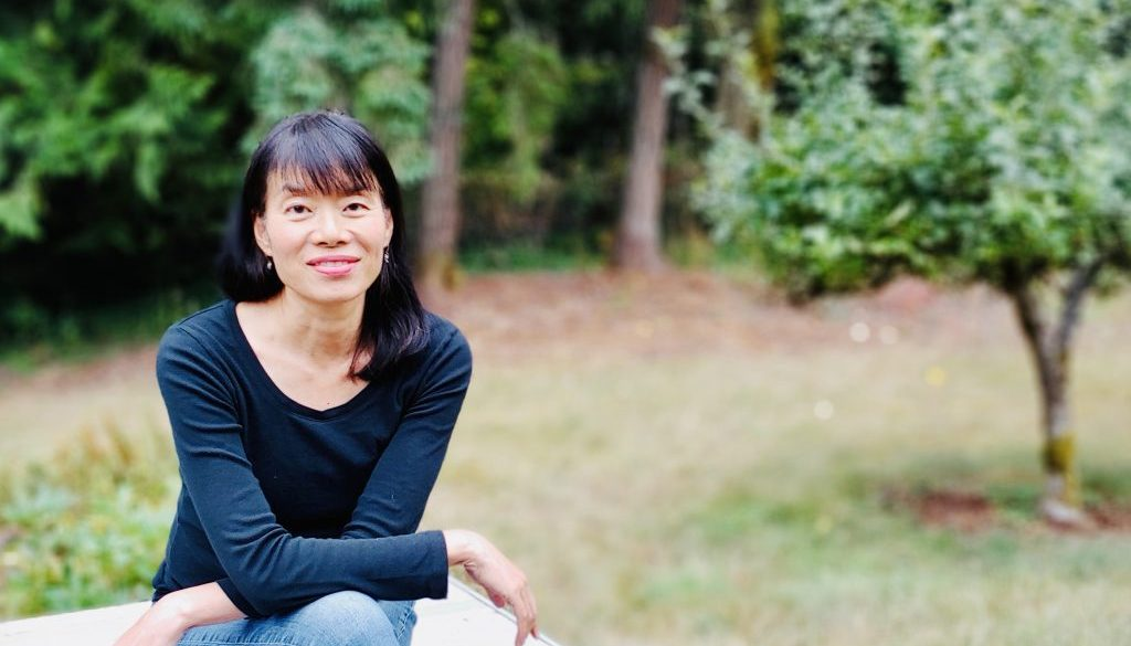Amy Lam sits in front of some trees.