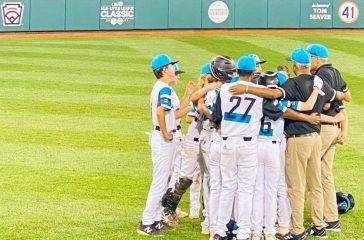 Eastlake team huddle on World Series field.