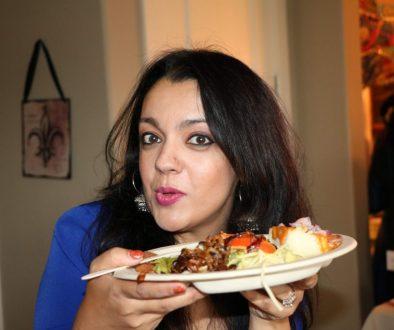 Venu Sareen holds a plate of food.