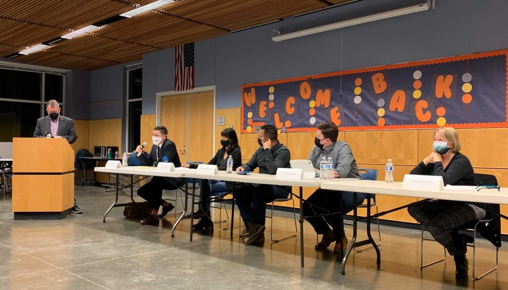 Candidates sit for candidate forum.