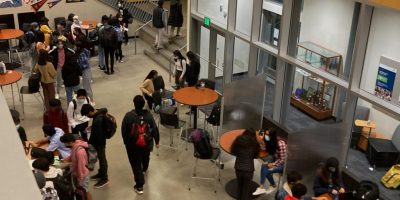 Students walking school hallway.